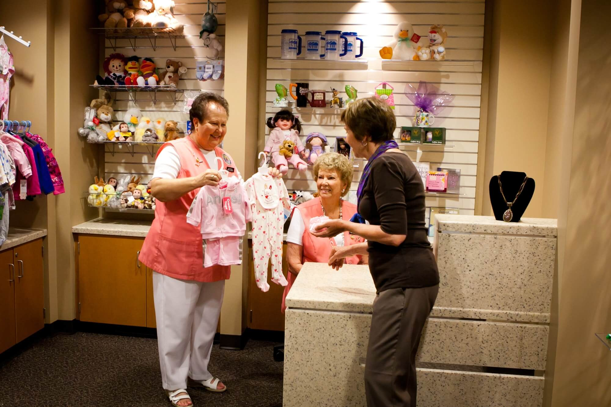 NIH Auxiliary President Judy Fratella shows a patron some of the baby gifts available at the Gift Shop as Auxiliary member Shirley Stone looks on. Photo by Michael Cooke