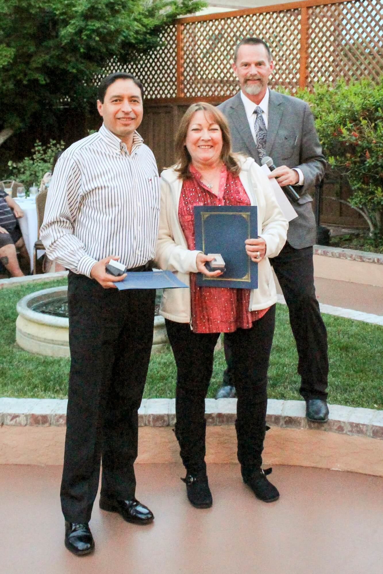 Dr. Kevin Flanigan presented 15-year pins of service to Oscar Morales and Linda Little.